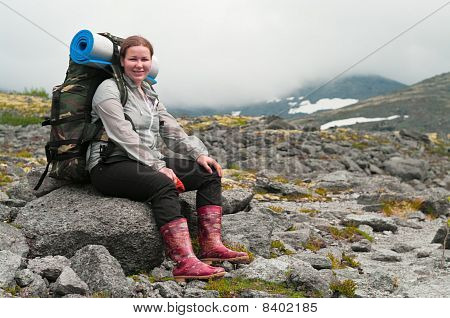 Backpacker A Young Woman Sitting On Rock In Mountains