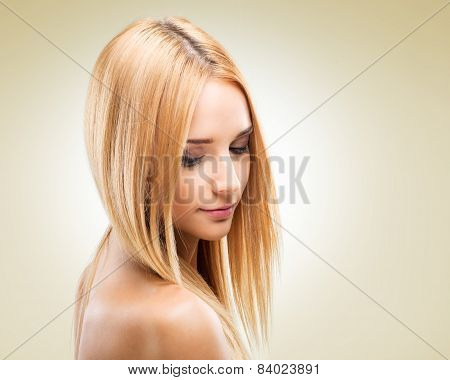 Beautiful blonde woman in profile looking down on a light background