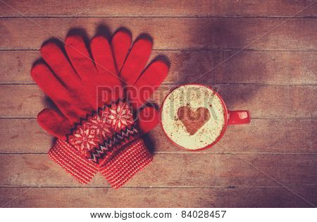 Gloves And Cup With Coffee And Shape Of The Cacao Heart On It.