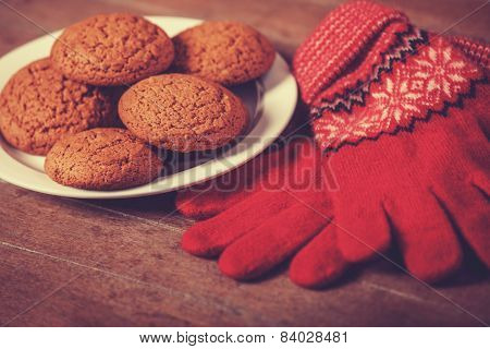 Red Gloves And Cookie At Wooden Table.