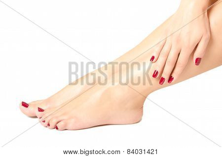 Beautiful female feet and hands with red manicure