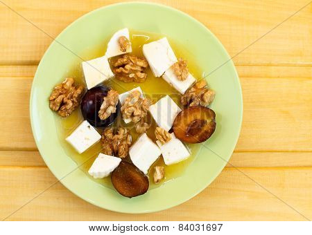 fruity honey salad with cheese on wooden table