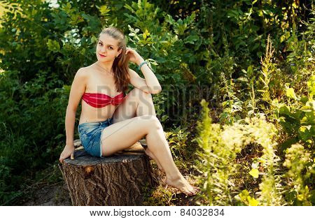 young blond woman at nature, sitting on stump