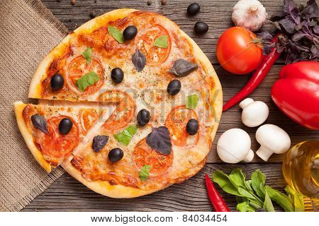 Sliced Italian Pizza Margherita With Tomatoes, Olives And Basil Top View