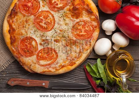 Traditional Pizza Margherita With Tomatoes, Olive Oil And Basil Close Up On Rustic Background
