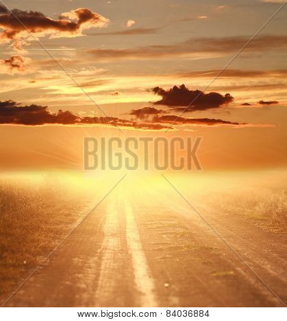 Colorful Sunset Over Country Road On The Background Of Dramatic Skyand Blinding Rays Of Light