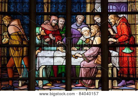 BRUSSELS BELGIUM - JULY 26 2012: Stained Glass window depicting the local legend of Jews stealing sacramental bread in the Cathedral of Brussels Belgium.