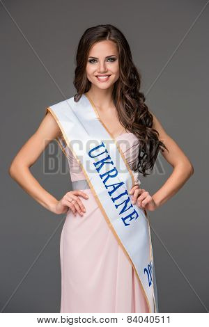 Beautiful young brunette woman with her hair posing in a i pink dress. Studio, on gray background