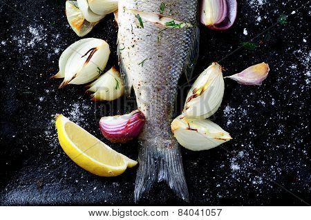 Baked Fish With Lemon And Onion On A Baking Sheet