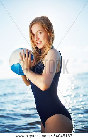 Young woman posing on the beach with volleyball