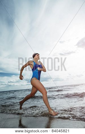 Young woman athlete running on the beach