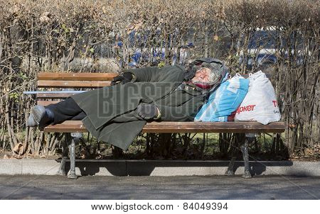 Homeless Woman Sleeping On A Bench