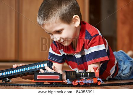 Little Boy Playing With Railway Lying On Floor