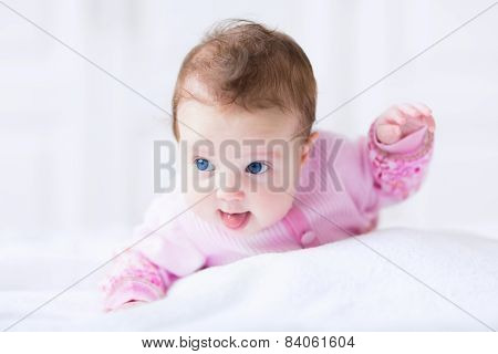 Cute Funny Baby Girl In A Pink Cardigan Trying To Crawl