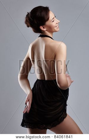 Rear view of smiling woman posing in sexy negligee