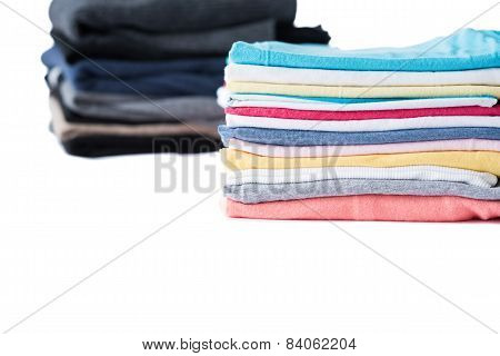Stack of winter pullovers and summer t-shirts