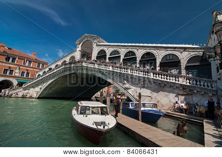 Rialto Bridge With Tourists And Boats On Grand Canal, Venice, Italy