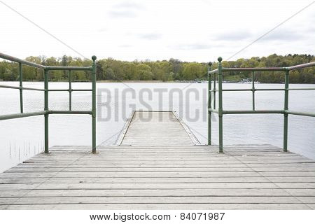 Wood pier with iron railing by lake