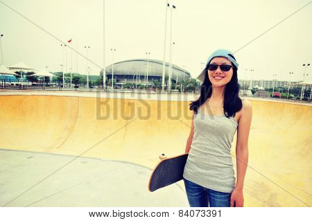 young woamn skateboarder hold a skateboard at skatepark