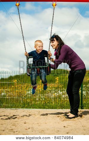 Mother And Son Having Fun On A Swing Outside