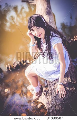A Cute Asian Thai Girl Is Sitting On A Tree Trunk On The Riverside Making Eye Contact In Dark Vintag
