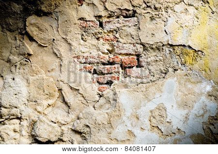 Old red brick  in cracked concrete wall