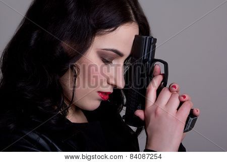 Portrait Of Beautiful Woman With Gun Over Grey