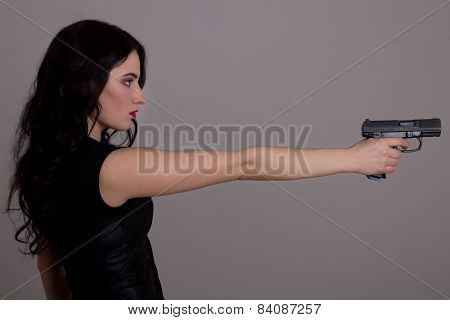Side View Of Young Beautiful Woman With Gun Over Grey
