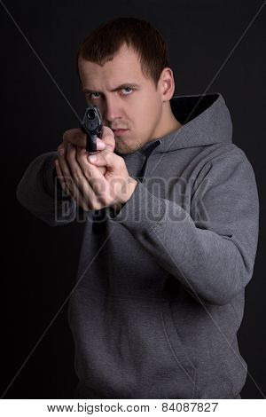 Young Man Criminal Aiming With Gun Over Grey
