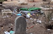picture of scourge  - A homeless man sleep on a grave in a grave yard - JPG