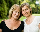 picture of mature adult  - Outside portrait of smiling happy mature woman with her adult daughter - JPG