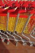 stock photo of supermarket  - Row of supermarket shopping cart trolleys at supermarket entrance - JPG