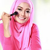 stock photo of blush  - portrait of cheerful young woman applying blush on - JPG