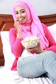 foto of muslimah  - portrait of young muslim woman enjoy eating popcorn on bed - JPG