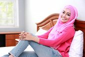 foto of muslimah  - portrait of young muslim woman relaxing body on bed - JPG