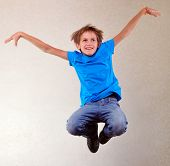 pic of sportive  - Portrait of a cute sportive cheerful happy boy with his hands up jumping and dancing - JPG