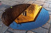 stock photo of manhole  - Reflection of blue sky and yellow house with fence in round puddle on the manhole cover surrounded by pedestrian pavement on a sunny day - JPG