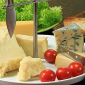 stock photo of cheese platter  - Various types of cheese on ceramic platter - JPG