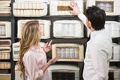 picture of mattress  - The young salesman tells the customer about quality mattresses in the store - JPG