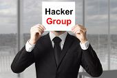 stock photo of vpn  - businessman in office hiding face behind sign hacker group - JPG
