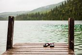 pic of platform shoes  - Flip flops on a Dock in front of a Turquoise Water Lake in the Wild Nature - JPG