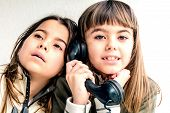 picture of 7-year-old  - Seven year old girl talking on the old vintage phone and her sister eavesdropping her conversation - JPG