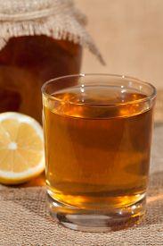 stock photo of pro-life  - Kombucha superfood pro biotic tea fungus beverage in glass with lemon on white background - JPG