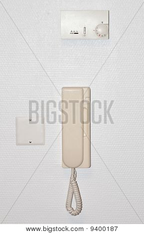 Beige intercom on a white wall