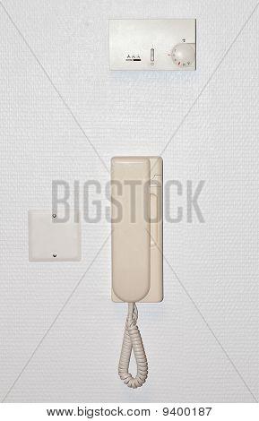 Beige intercom on a white wall
