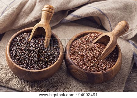 Red, black quinoa seeds on a wooden background