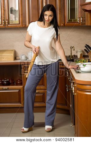 housewife holding a rolling pin. It stands in the kitchen