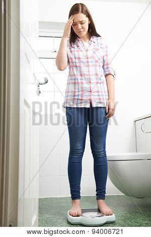 Unhappy Teenage Girl Standing On Bathroom Scales
