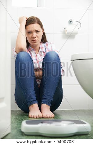 Unhappy Teenage Girl Looking At Bathroom Scales