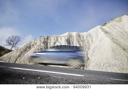 Blue car traveling in a arid landscape of Spain